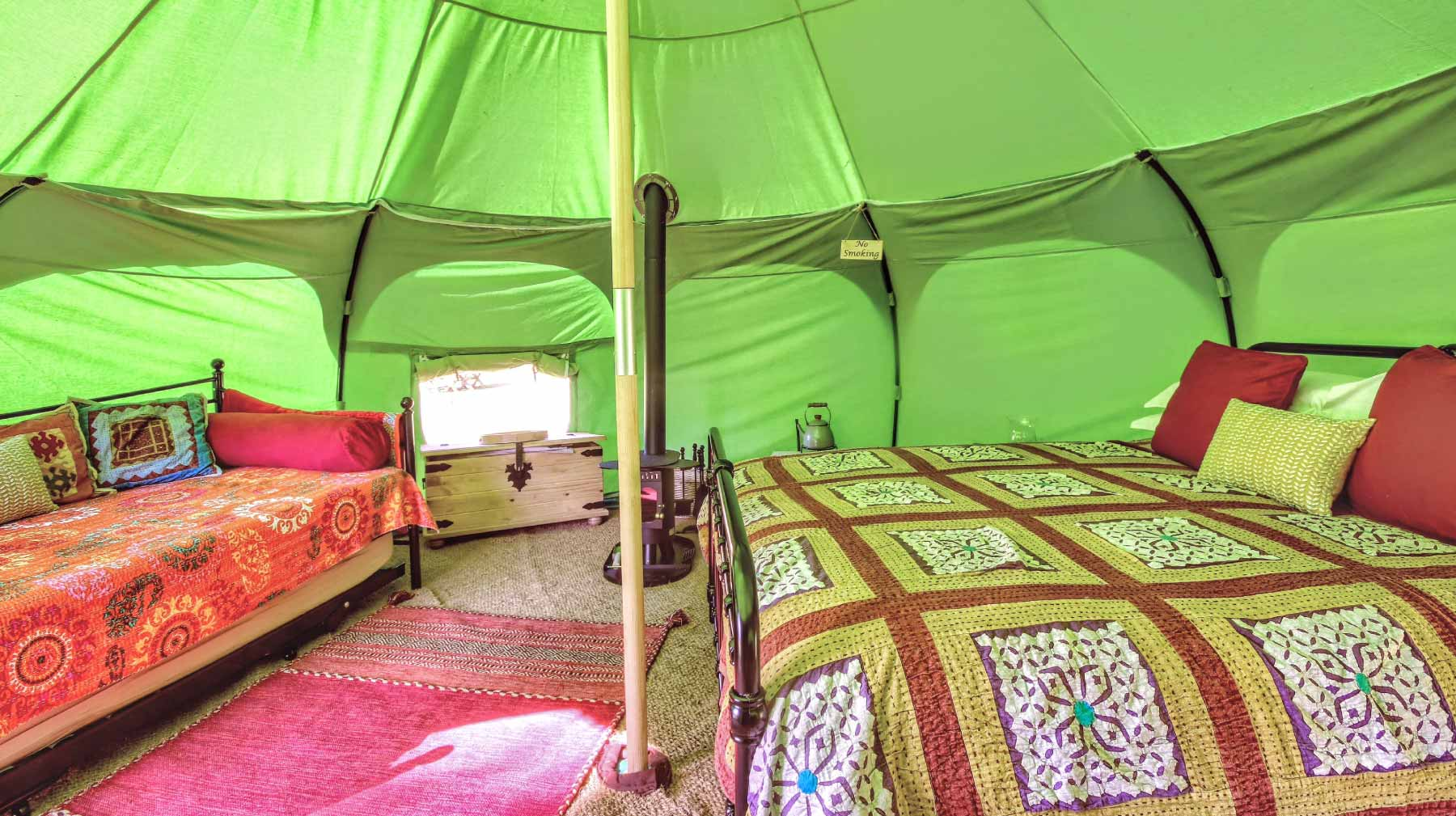 inside a lotus belle tent showing a large bed and sofa
