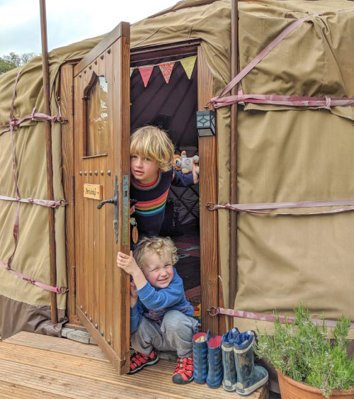 Happy children at the entrance of a family luxury yurt