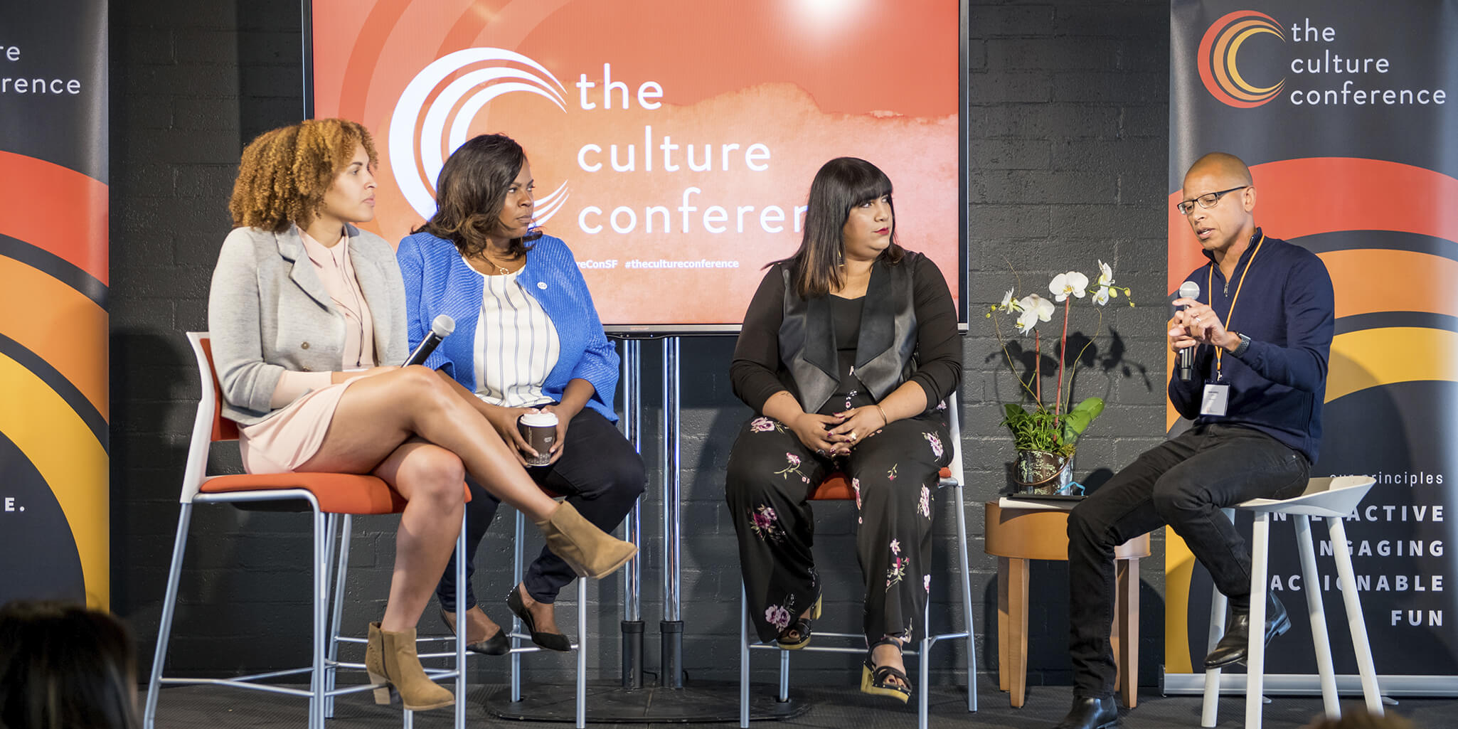 3 women and 1 man on stage during a panel discussion