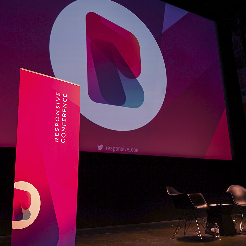 Photo of the Responsive Conference Main Stage, with branded screen design and sigange