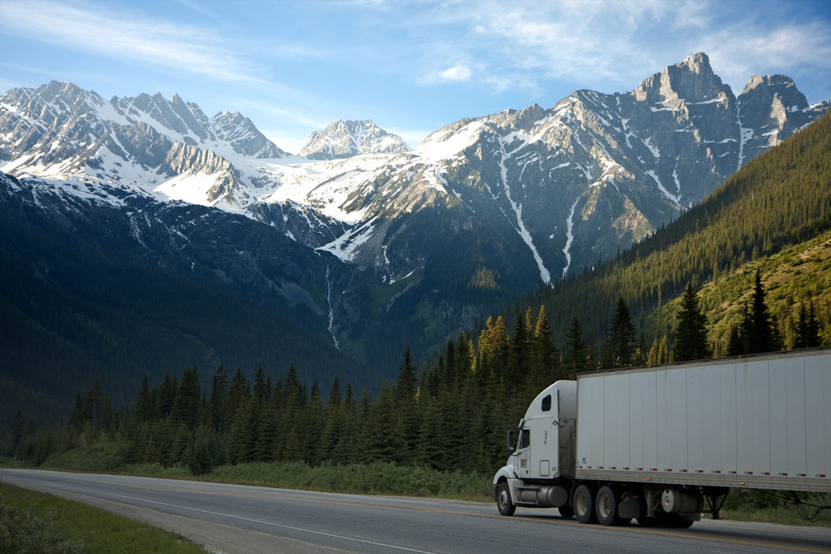 Mountains, trees and truck on road