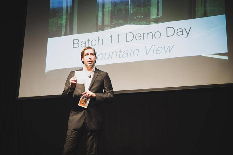 A man presenting in a demo day holding a card and a presentation in the background