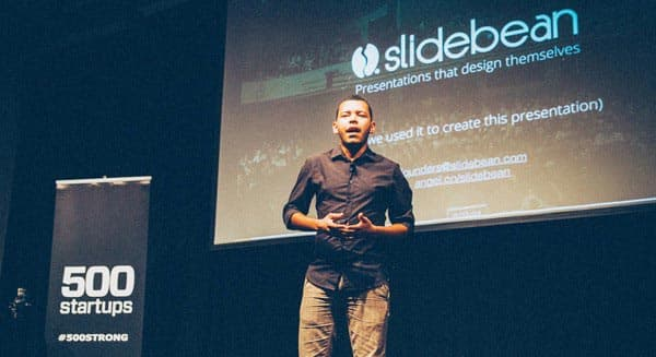 Slidebean CEO Caya speaking during his demo day at 500 startups. A Slidebean slide in the background