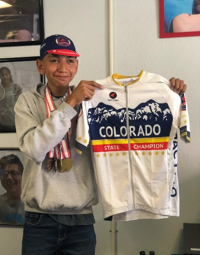 Francisco smiling while holding his Colorado State Championship Jersey and wearing all his cycling medals