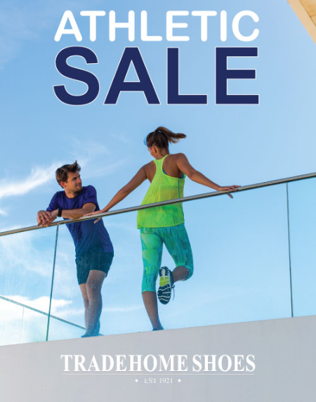 Two people in athletic clothes leaning on a glass railing