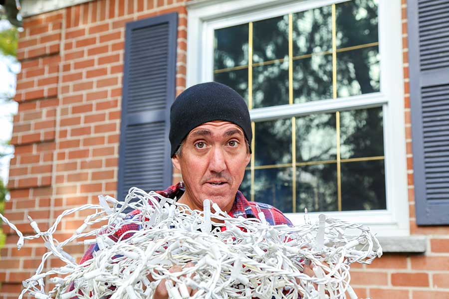 frustrated homeowner with tangled christmas lights