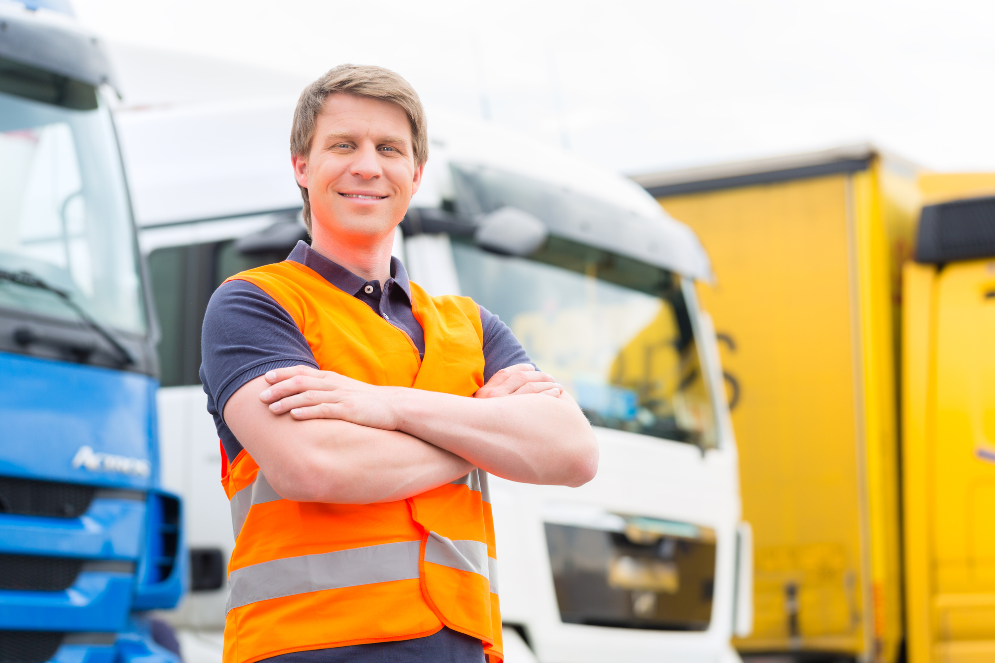 Fleet manager stands in front of trucks