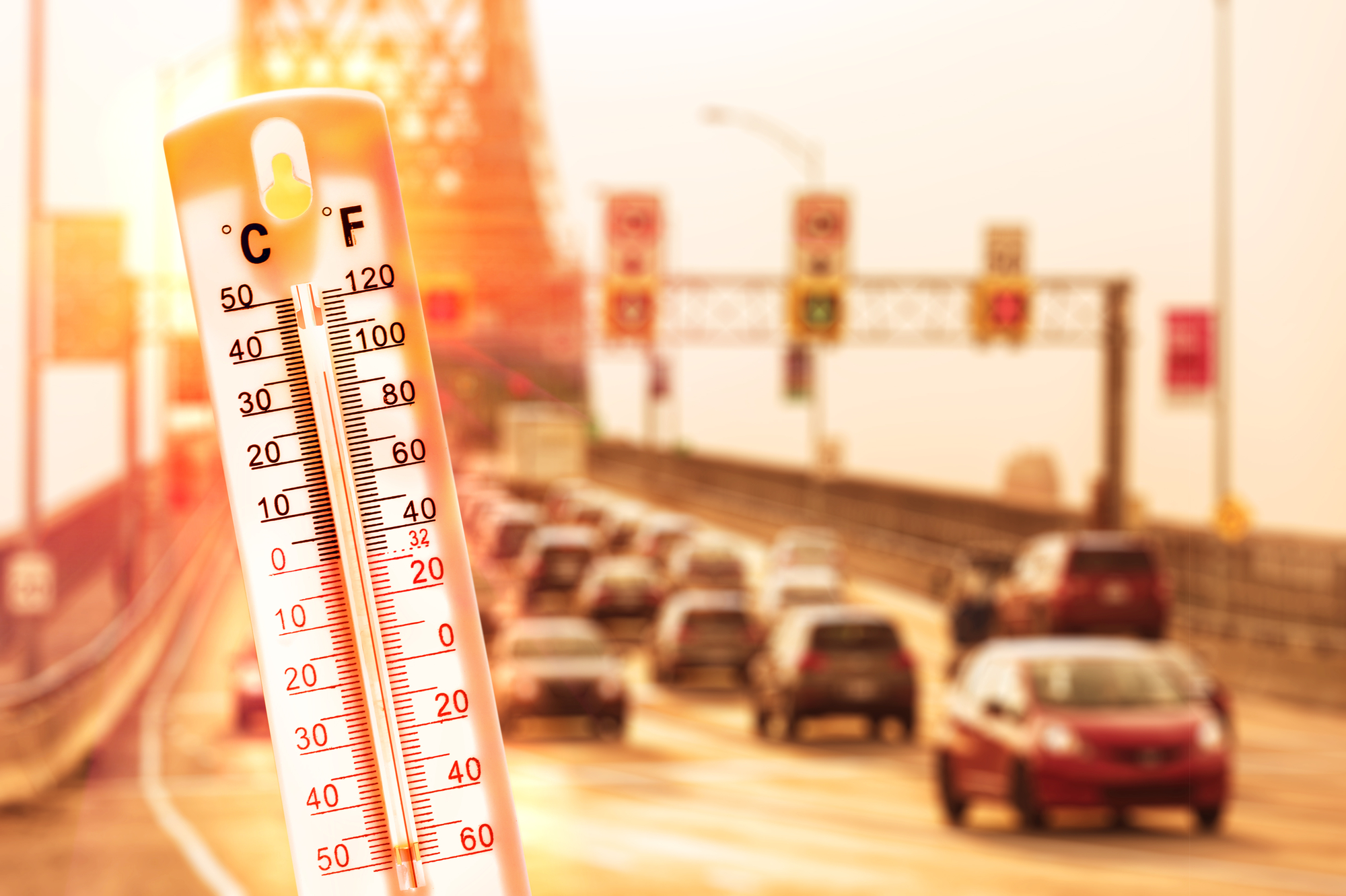 Thermometer shows high temp with traffic in the background
