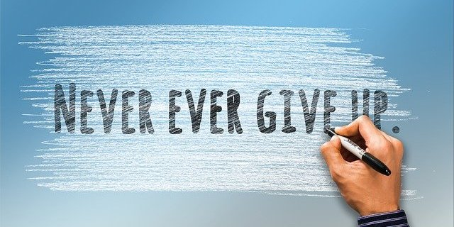 Writing on a wall that says, 'Never ever give up'