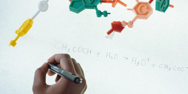 A student writing a chemical formula