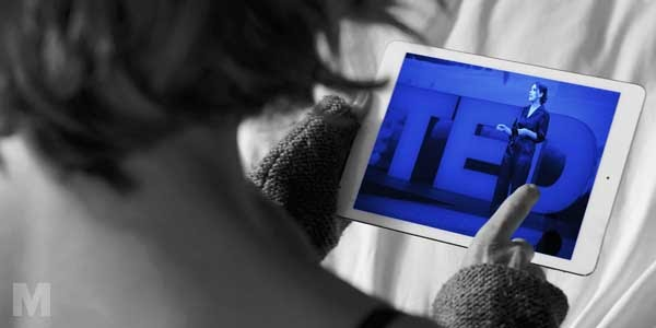 A person watching a TED video on a tablet device