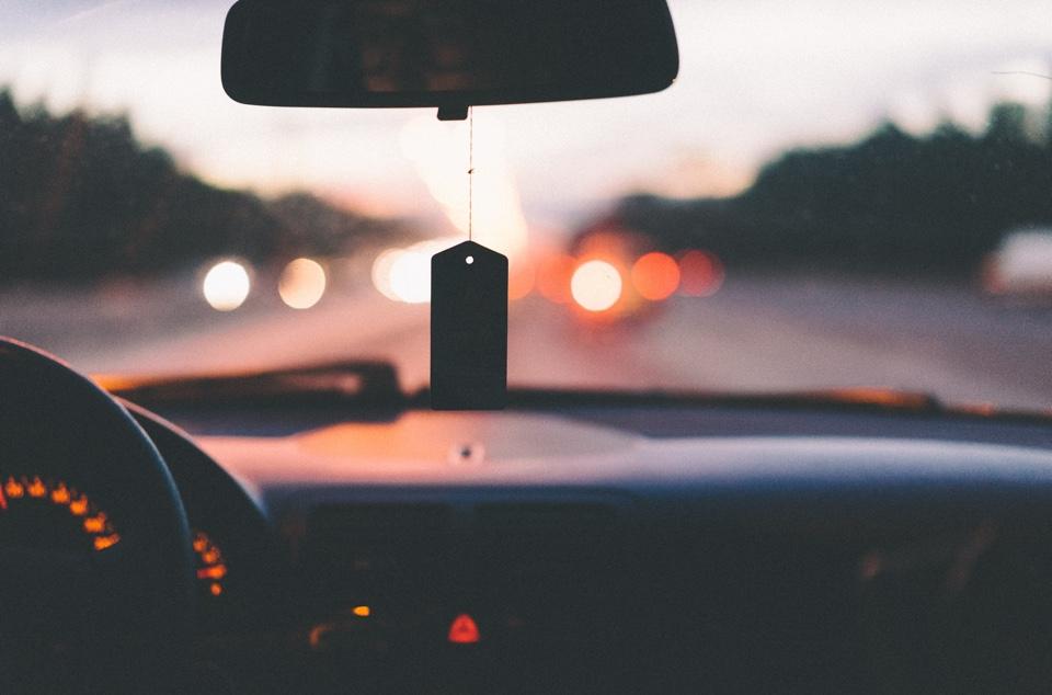 Blick durch die Windschutzscheibe eines Autos auf eine Straße im Sonnenuntergang