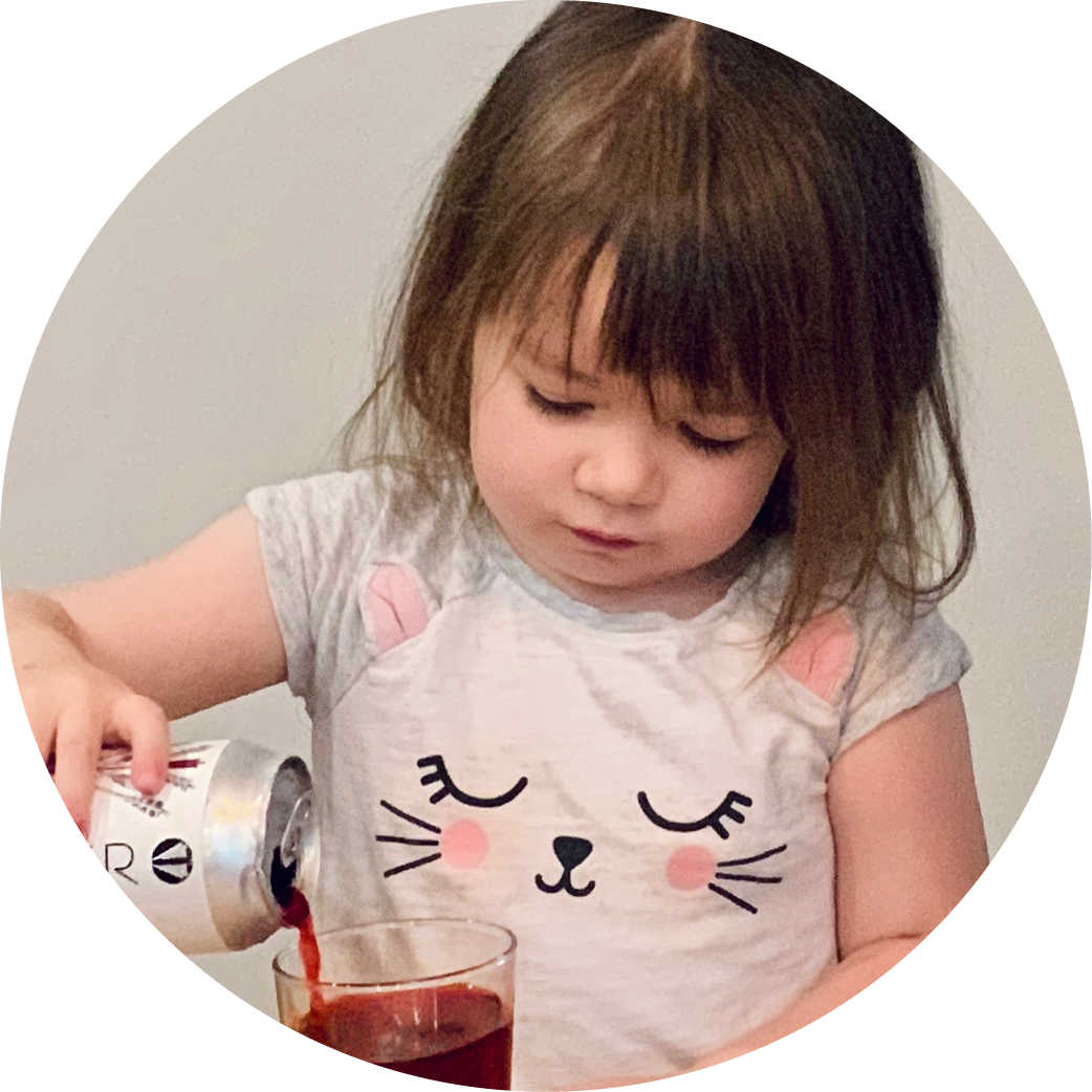 A circular picture of a small child pouring a decaf Quivr.