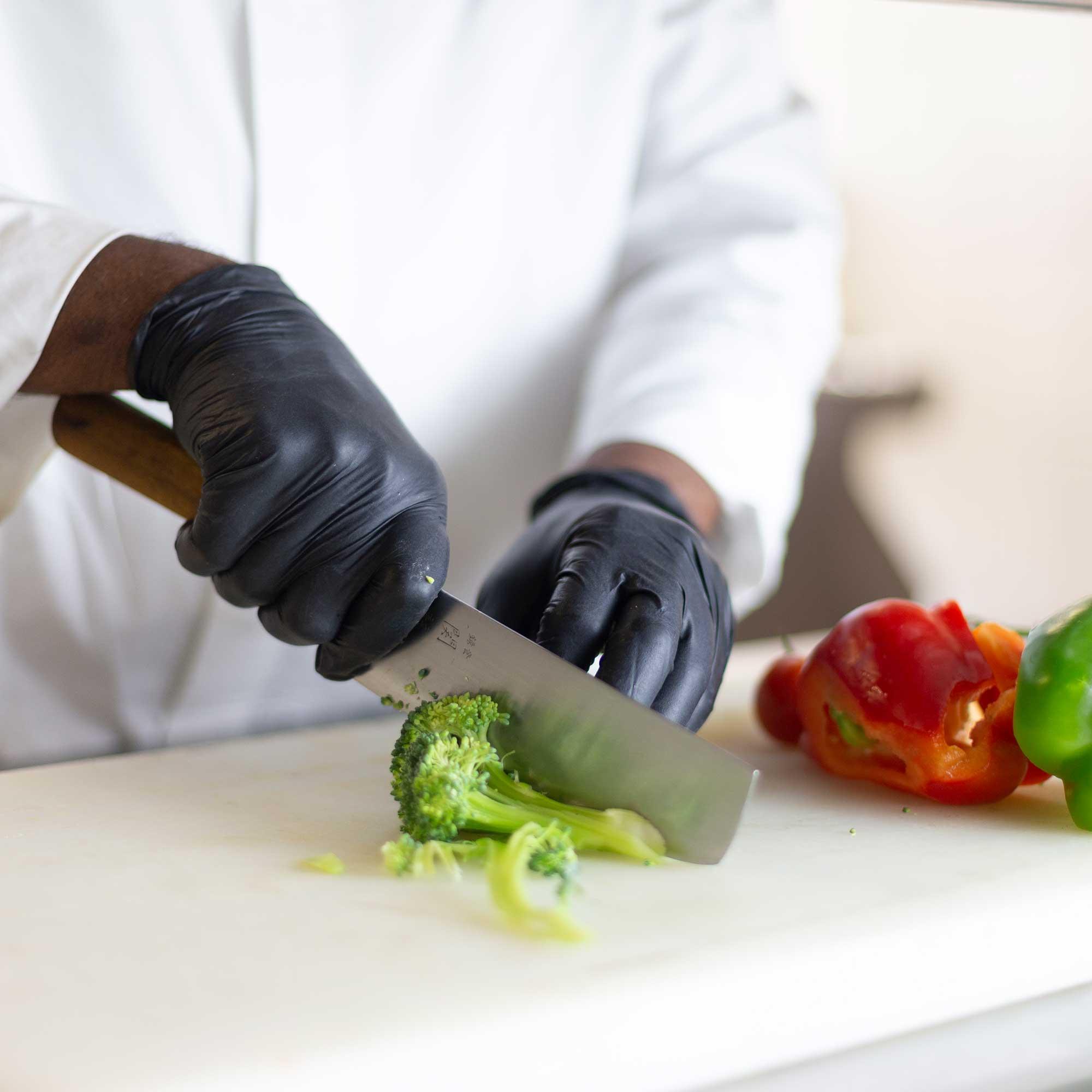 Koch schneidet frisches Gemüse im Restaurant Akrams