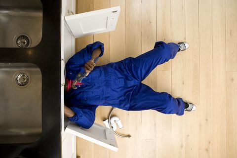 Plumber working under kitchen sink, overhead view