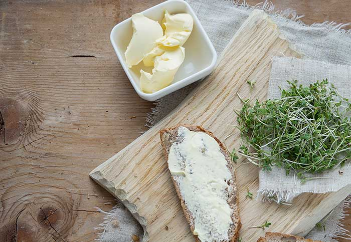 cannabis infused butter and cream cheese on morning toast with sprouts on wooden table
