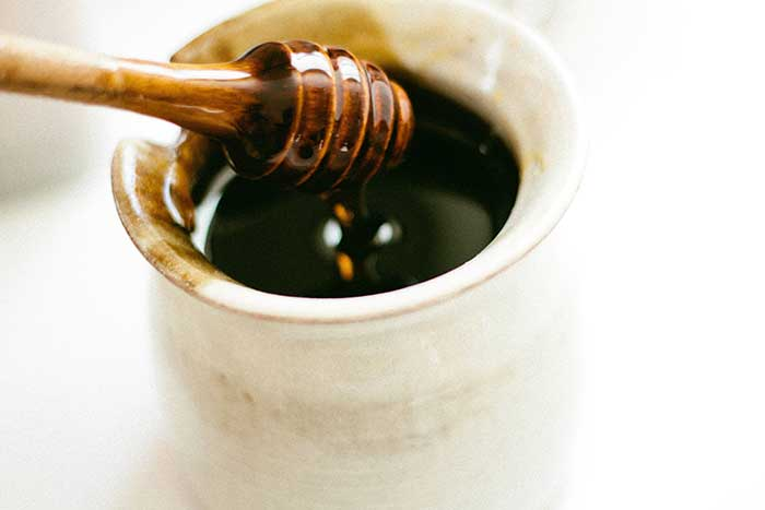 cannabis infused honey traditional wooden spoon and honey pot