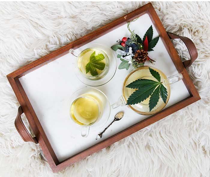 cannabis infused drinks tea and tea cups on fur blanket pretty flower arrangment