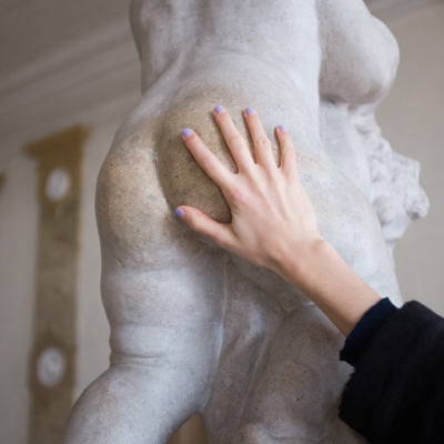 hand caressing the butt of a statue suggesting butt play