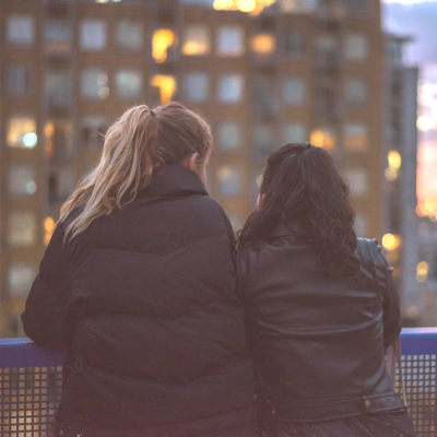 lesbian couple standing together looking at a view after a successful opening date