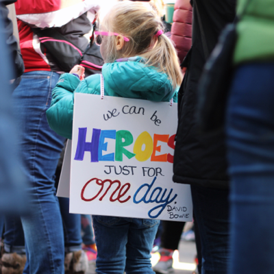 "child supporting LGBTQ rights and gender transition at a rally with a sign that says ""we can be heroes just for one day"""