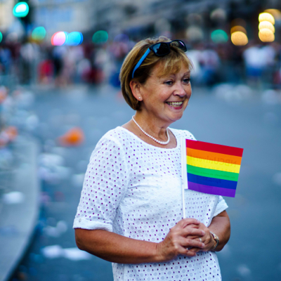 middle age woman smiling with a rainbow flag showing support for LGBTQ rights and gender transition