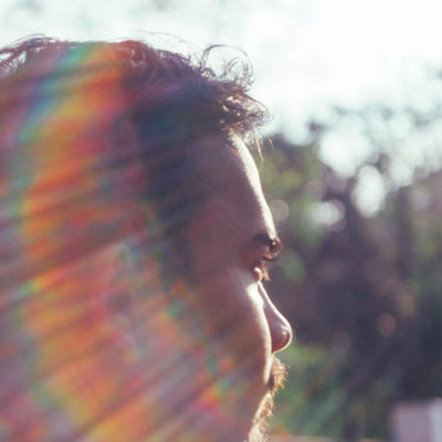 man with rainbow lens flare representing questioning bisexuality
