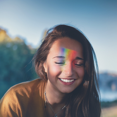 "women with rainbow reflected on her forehead representing the question ""am I bisexual?"""