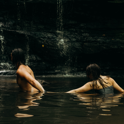 man leading a women through the water in a lagoon
