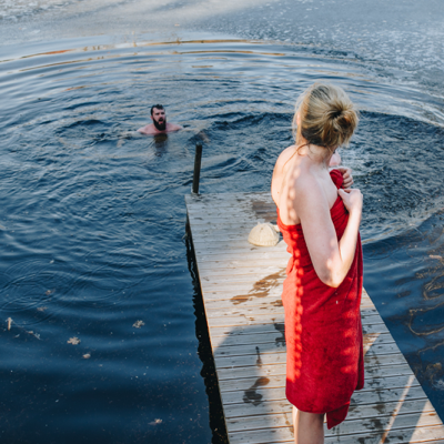 man swimming in the water and woman on the pier deciding whether to join