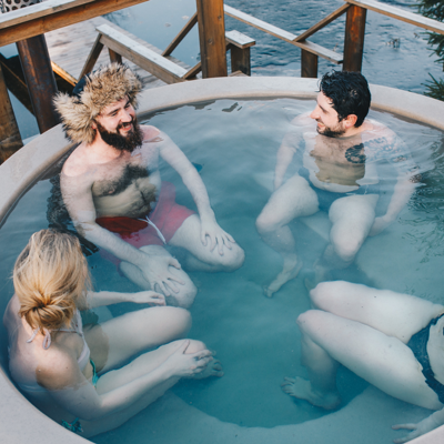 two couples talking in a hot tub together