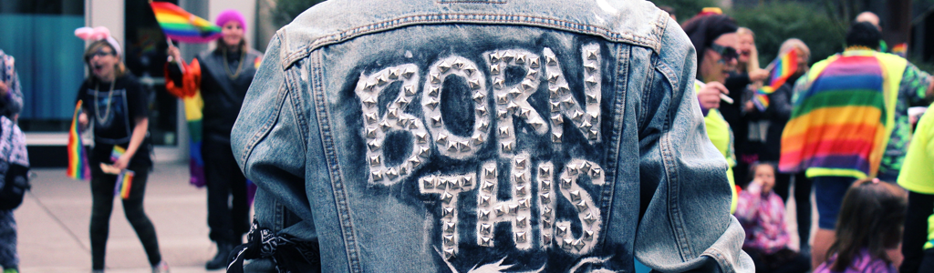 "back of a person wearing a jean jacket that says ""born this way"""