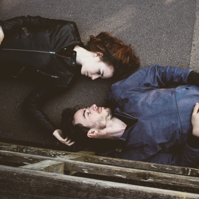 couple laying on the ground while the woman rubs the man's head in loving support