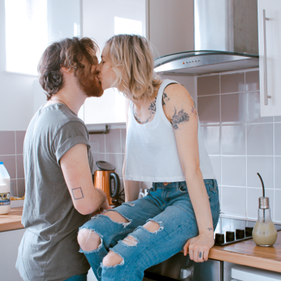 man and woman kissing on the kitchen counter as they begin spontaneous sex