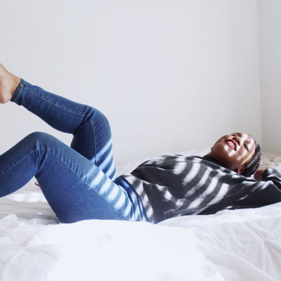 woman laying on her bed looking relaxed after learning how to orgasm