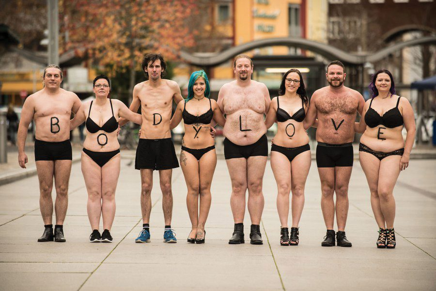 "man and woman with diverse bodies standing together with ""body love"" written on them"