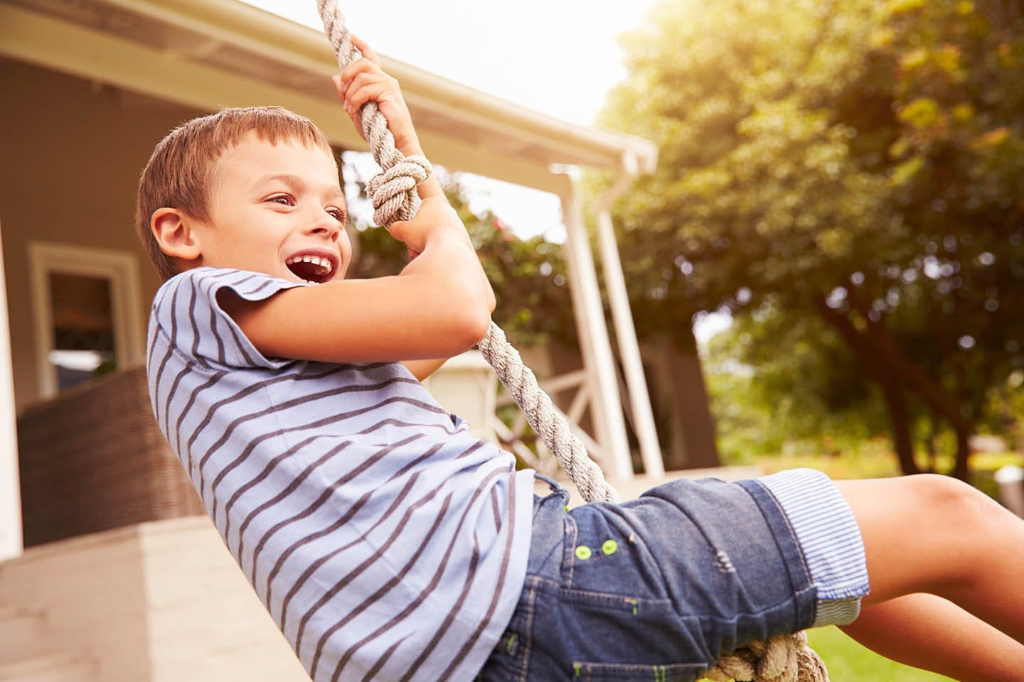 Young boy swinging on a rope