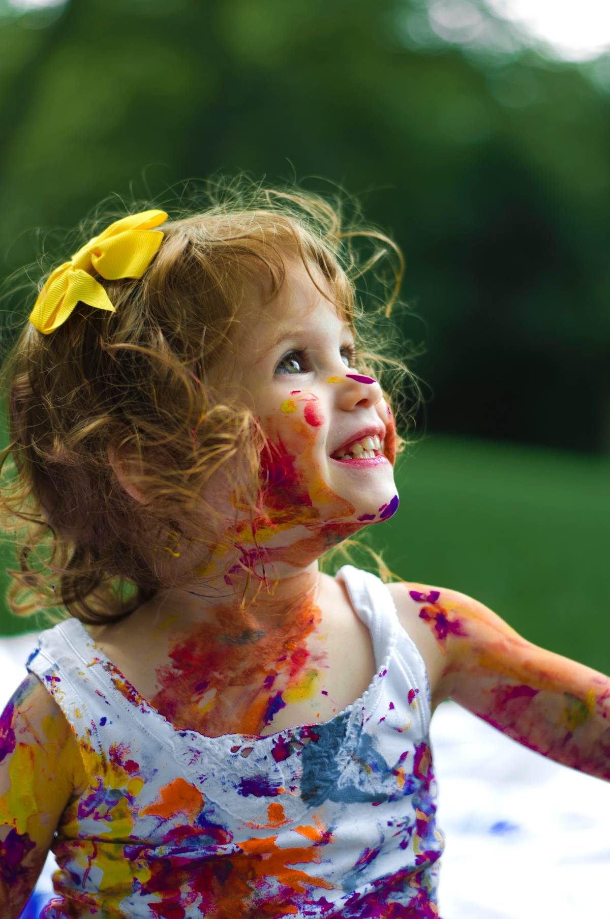 Child smiling up at the sky with paint all over her body