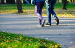 Kahden ihmisen kävelevät jalat tiellä, jota ympäröi puistomaisema.