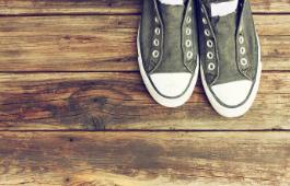 Harmaat Converse-kengät ilman nauhoja puulattialla.
