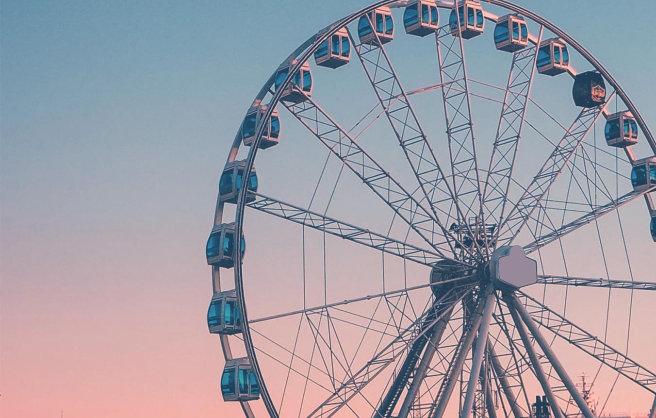 Maailmanpyörä, jonka taustalla vaaleanpunainen ja -sininen taivas