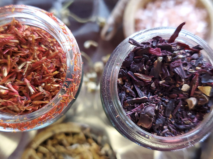 Two glass jars with colorful herbs
