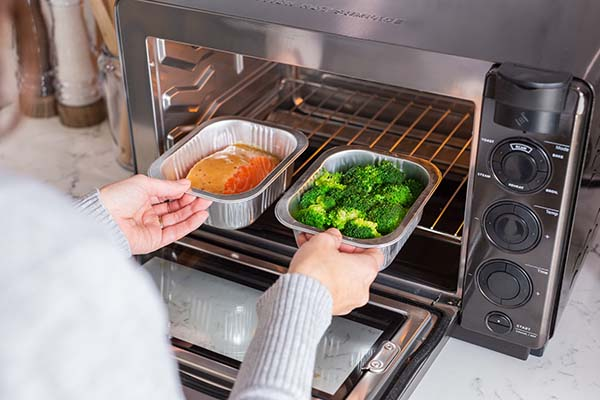 A person inserting salmon and broccoli in meal trays into the Tovala Oven.