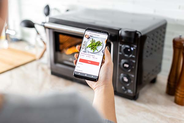 A person using the Tovala App to start cooking the roasted asparagus recipe.