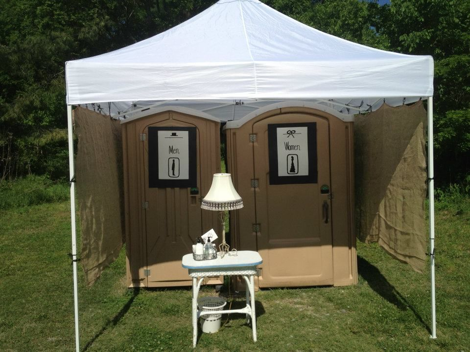 Porta Potties covered by a white event tent with a small white table and a lamp just outside
