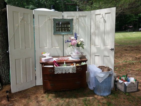 outdoor event design with white doors an antique chest of drawers with flowers and decor atop