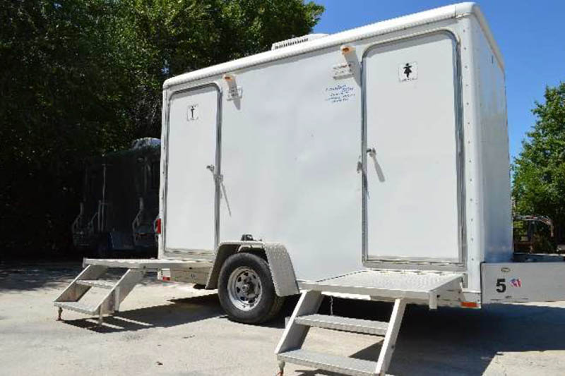 white bathroom trailer with two stalls