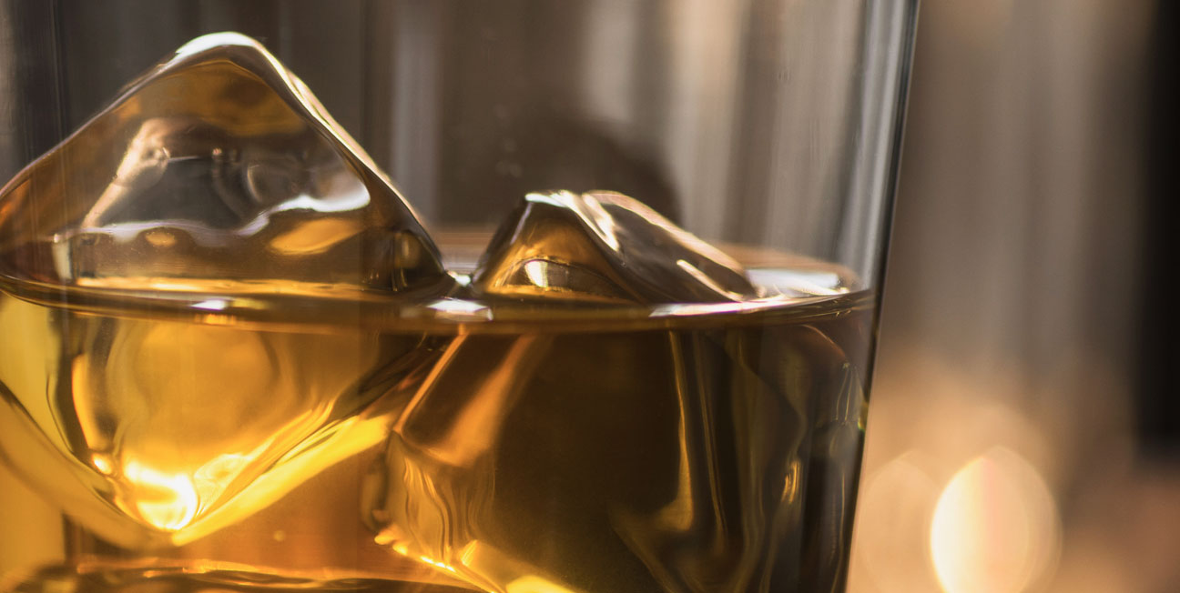 glass with bourbon and ice cubes