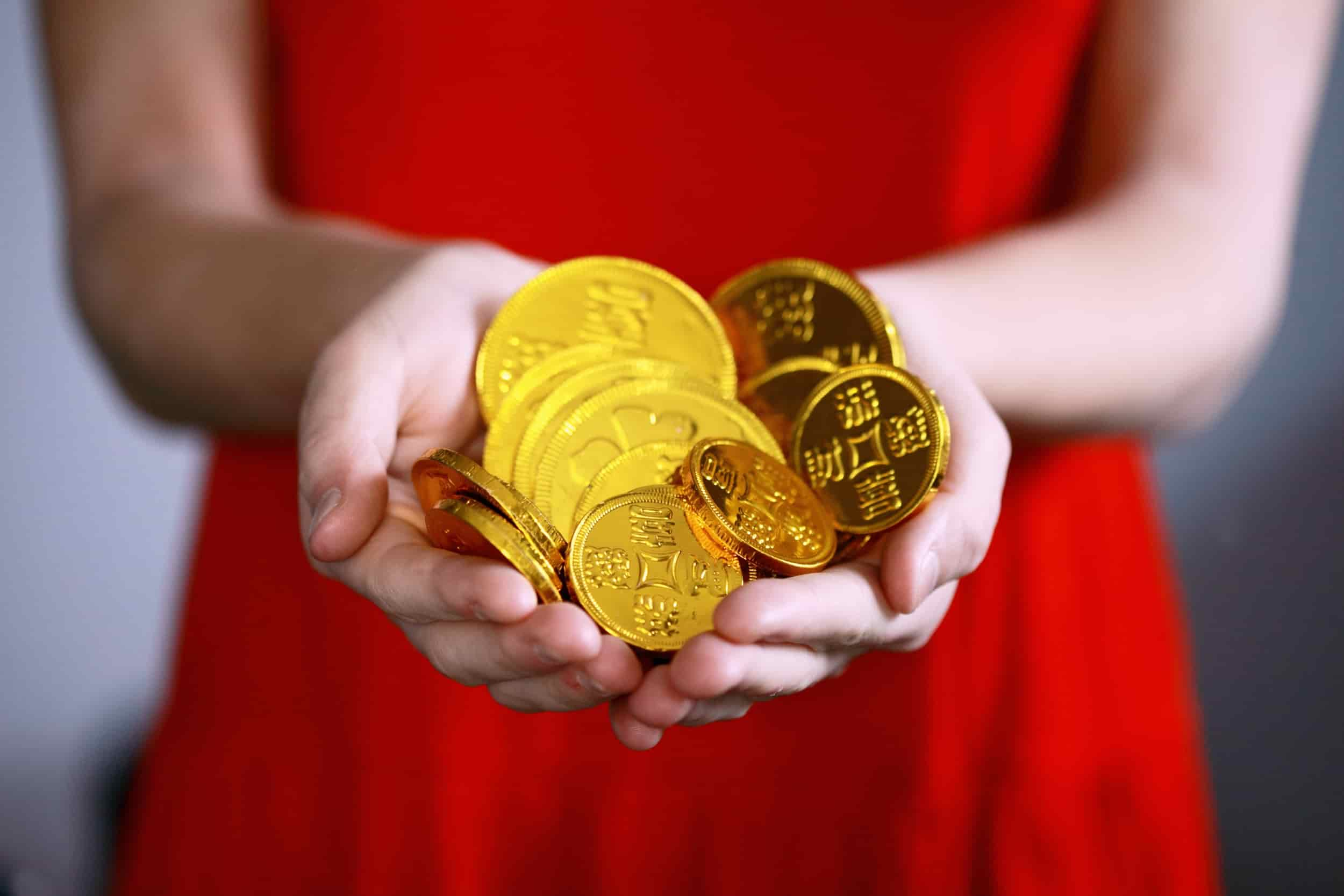 female office manager in red dress holding gold coins that she is responsible for managing