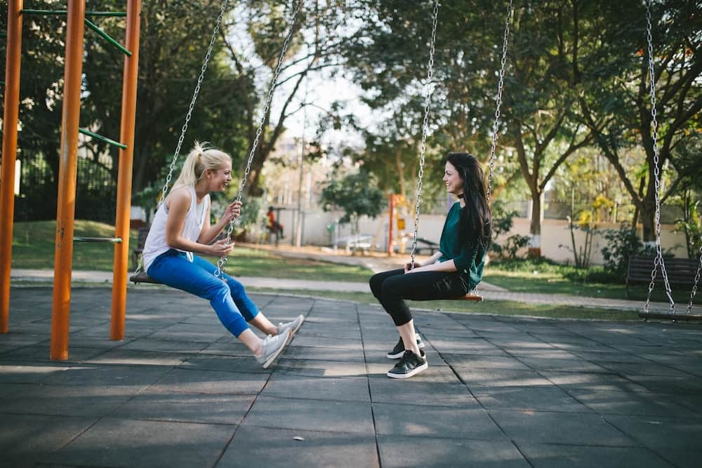 Two women on swings in a park outside facing each other while talking